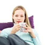 Young Woman Sitting and Holding a Cup of Coffee